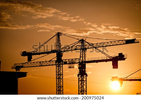Color picture of some cranes on a construction site, as dusk.