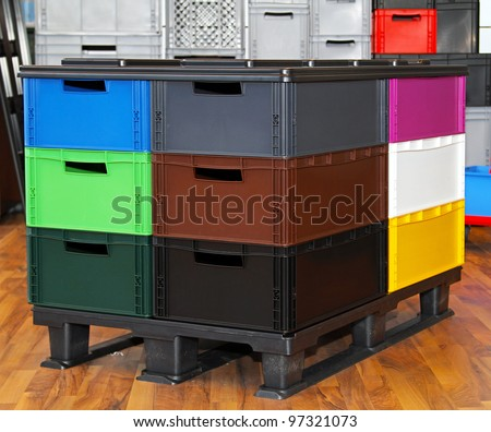 Color plastic crates and boxes at transportation pallet
