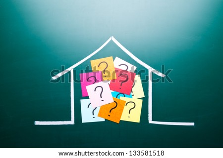 Color question mark in drawing house on blackboard - stock photo