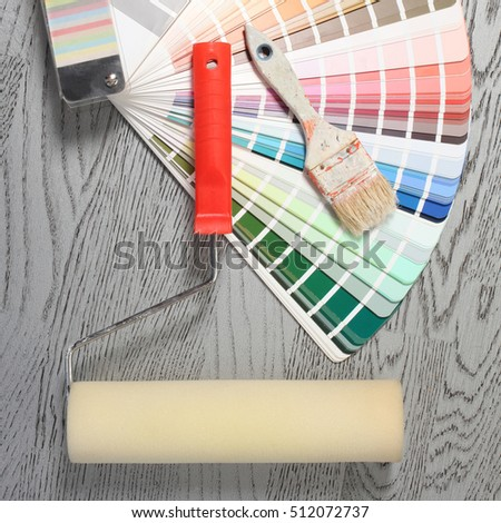 Color samples catalog, brush and roller on parquet