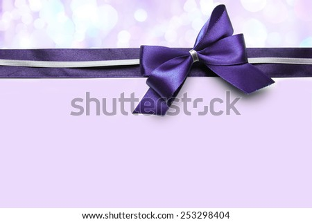 Color satin ribbon bow on purple background - stock photo