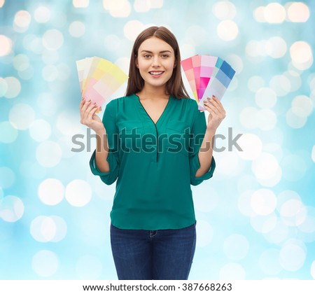 color scheme, decoration, design and people concept - smiling young woman with color swatches or samples over blue holidays lights background
