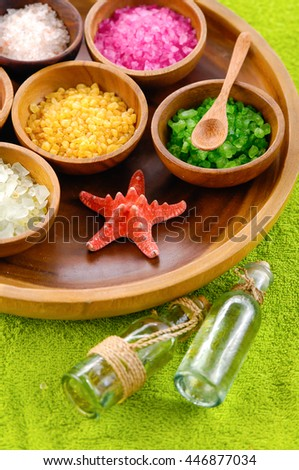 color sea salt in wooden bowl with oil, starfish on green towel - stock photo