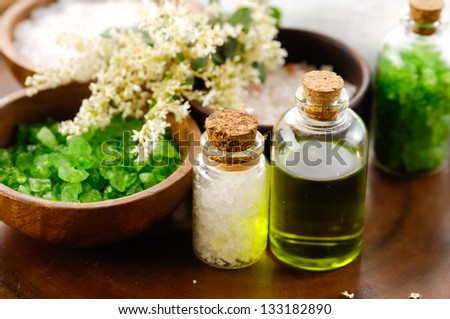 color sea salt in wooden bowl with salt with oil in glass on wooden bowl - stock photo