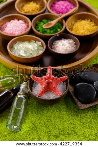 color sea salt in wooden bowl with stones, oil on green towel - stock photo