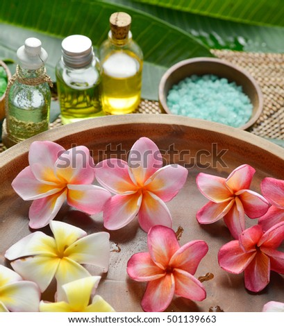 color sea salt with frangipani in wooden bowl with, oil on mat