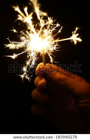 Color shot of a hand holding a sparkler. - stock photo
