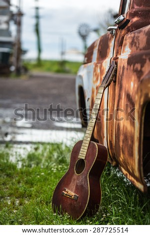 Color shot of an old acoustic guitar leaning up against an old rusted truck after a rain parked in the grass in Clarksdale Mississippi