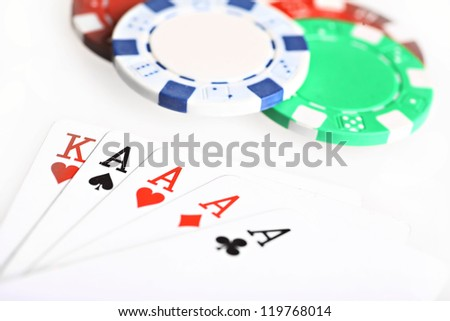 Color shot of four aces, a king and poker chips.