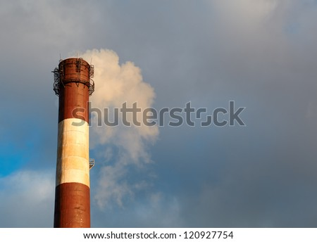 Color smoke comes out of the smokestacks at sunset. Air pollution. - stock photo