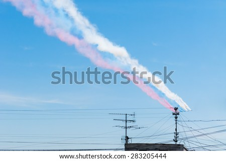 Color smokes in the form of Russian flag (tricolor) made by jet aircrafts against blue sky background.   - stock photo