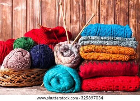Color threads, knitting needles and clothes on the wooden table - stock photo