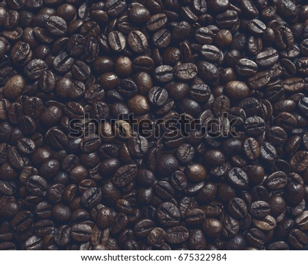 Color toned coffee beans on dark background.