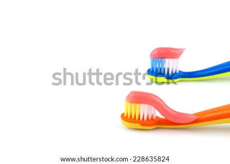 Color toothbrushes with pink toothpaste isolated on white background - stock photo