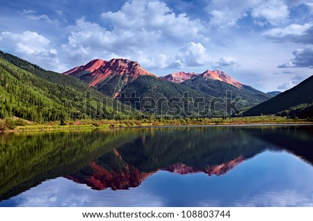 Colorado San Juan Skyway, Red Iron Peaks Reflecting In A Crystal Clear High Mountain Lake With Conifer Pines and Aspens, USA - stock photo