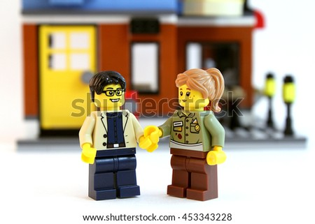 Colorado, USA - July 16, 2016: Studio shot of LEGO guy and girl holding hands in front of doorway to their new home. Shot isolated on white background. - stock photo