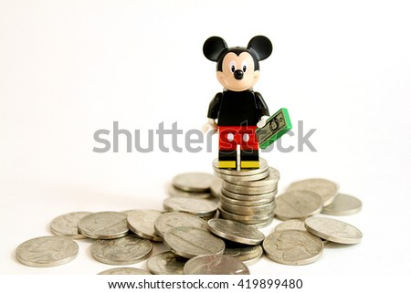 Colorado, USA - May 13, 2016: Studio shot of LEGO minifigure Mickey Mouse on top of a pile of money isolated on white background. - stock photo