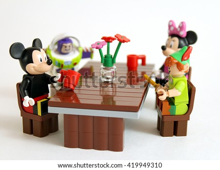 Colorado, USA - May 13, 2016: Studio shot of LEGO minifigure Mickey Mouse. Peter Pan, Buzz Lightyear, and Minnie Mouse all sitting at a table together.  - stock photo