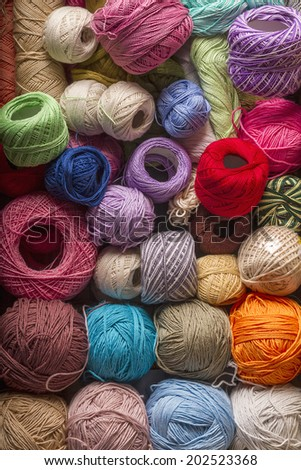 Colored balls of wool in an old suitcase