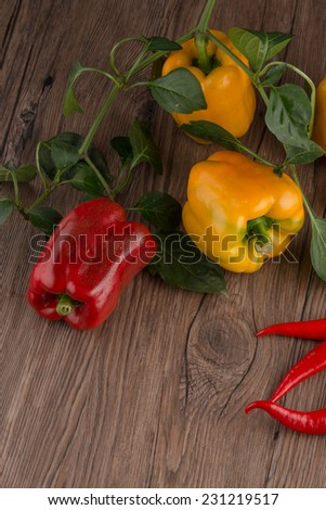 Colored bell peppers on old wooden table.
