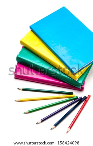 colored books and pencils on white background