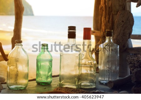 Colored bottles standing on counter at old bar by the sea