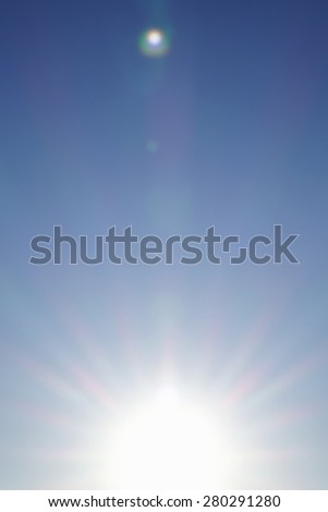 Colored bright rays of sunrise. Blurred abstract background of sky.