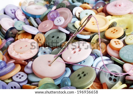Colored buttons and needle with thread - stock photo