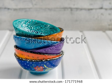 Colored ceramic dish on wooden table - stock photo