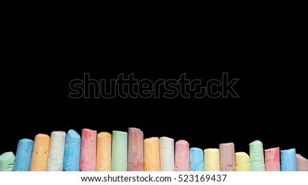 Colored chalks aligned on blackboard