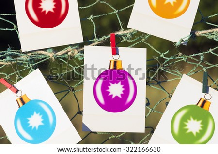 colored christmas balls photographs polaroid on the beach at sunset - stock photo
