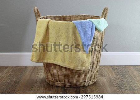 Colored cloth in a wooden basket on a wooden floor - stock photo