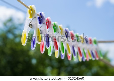 colored clothespins on rope - stock photo