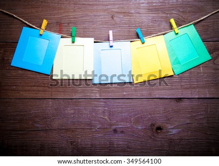 Colored clothespins with photo frames on rope on a wooden table or board for background. Space for text. Toned. - stock photo