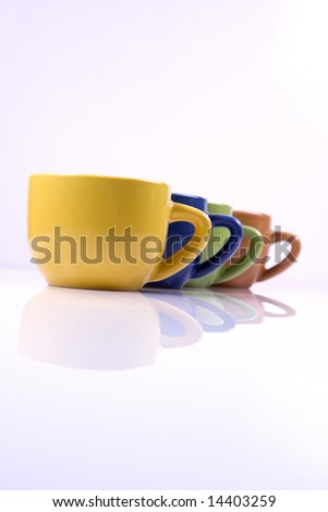 Colored coffee cups in line on white background