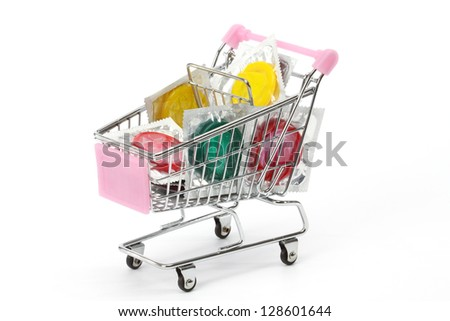 Colored condoms in shopping cart over white - stock photo