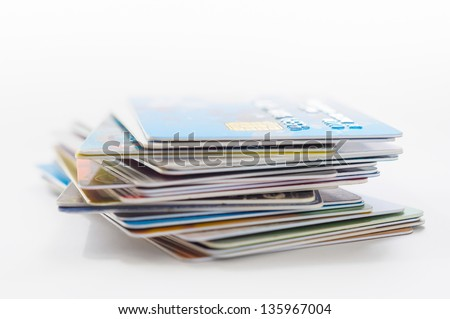 Colored credit cards stacked on white background - stock photo