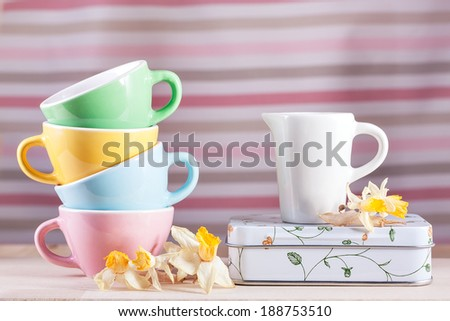 Colored cups with a pitcher and daffodils on wood vintage retro - stock photo