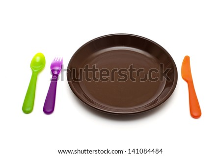 colored cutlery and a plate on white background - stock photo