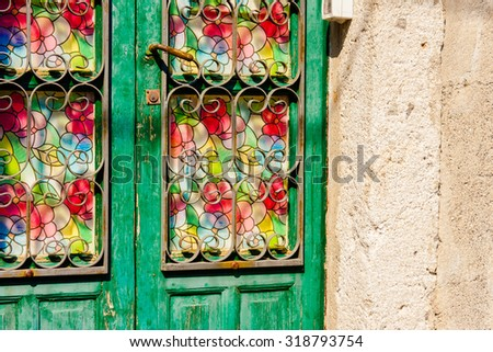 Colored door with mosaic glass and iron bars, typical mediterranean ornament. - stock photo