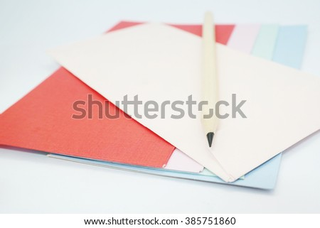 Colored drawing paper in a variety of colors in white isolated background with pencil - stock photo