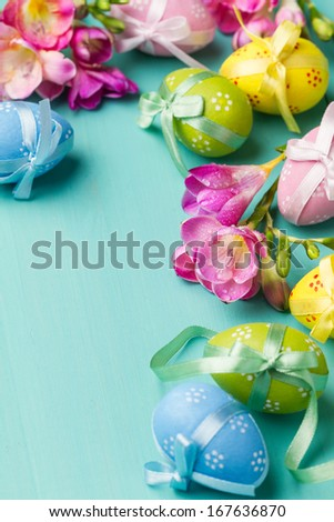Colored Easter eggs and flowers on a turquoise table (vertical shot) - stock photo