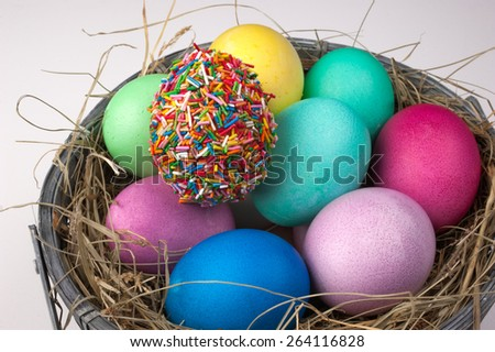 colored easter eggs and one covered with sprinkles in nest isolated on white  - stock photo