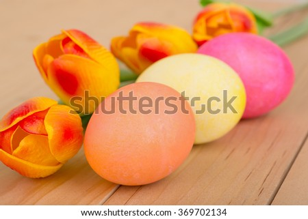 Colored Easter eggs and tulips on a wood table - stock photo