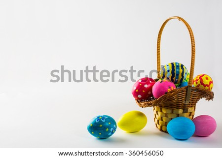 Colored Easter eggs in the basket on a white background. Easter background. Easter background. Easter symbol. Copy space - stock photo