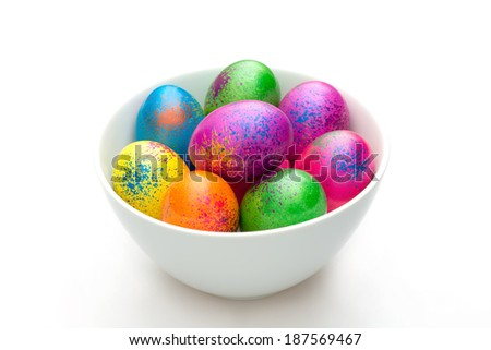 Colored Easter eggs in white ceramic bowl against white background
