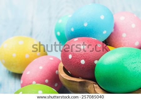 colored Easter eggs on wooden background. Focus on a red egg - stock photo