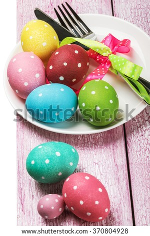 colored Easter eggs on wooden background. focus on the plate with eggs - stock photo