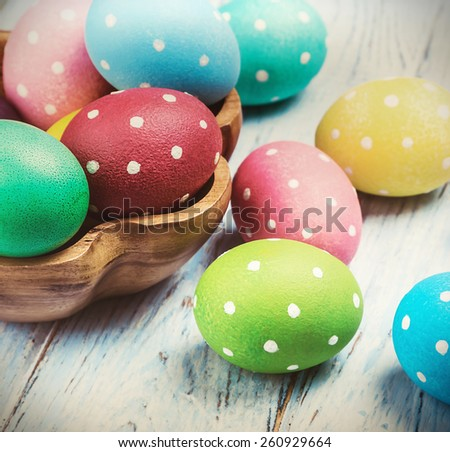 colored Easter eggs on wooden background. toned image - stock photo