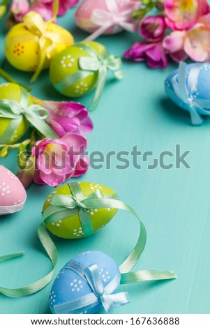 Colored Easter eggs with ribbons and flowers on a turquoise table (vertical shot) - stock photo